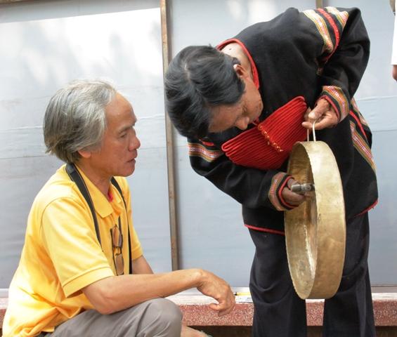 Nghệ nhân và du khách tìm hiểu chiếc chiêng do nghệ nhân Quảng Nam thực hiện